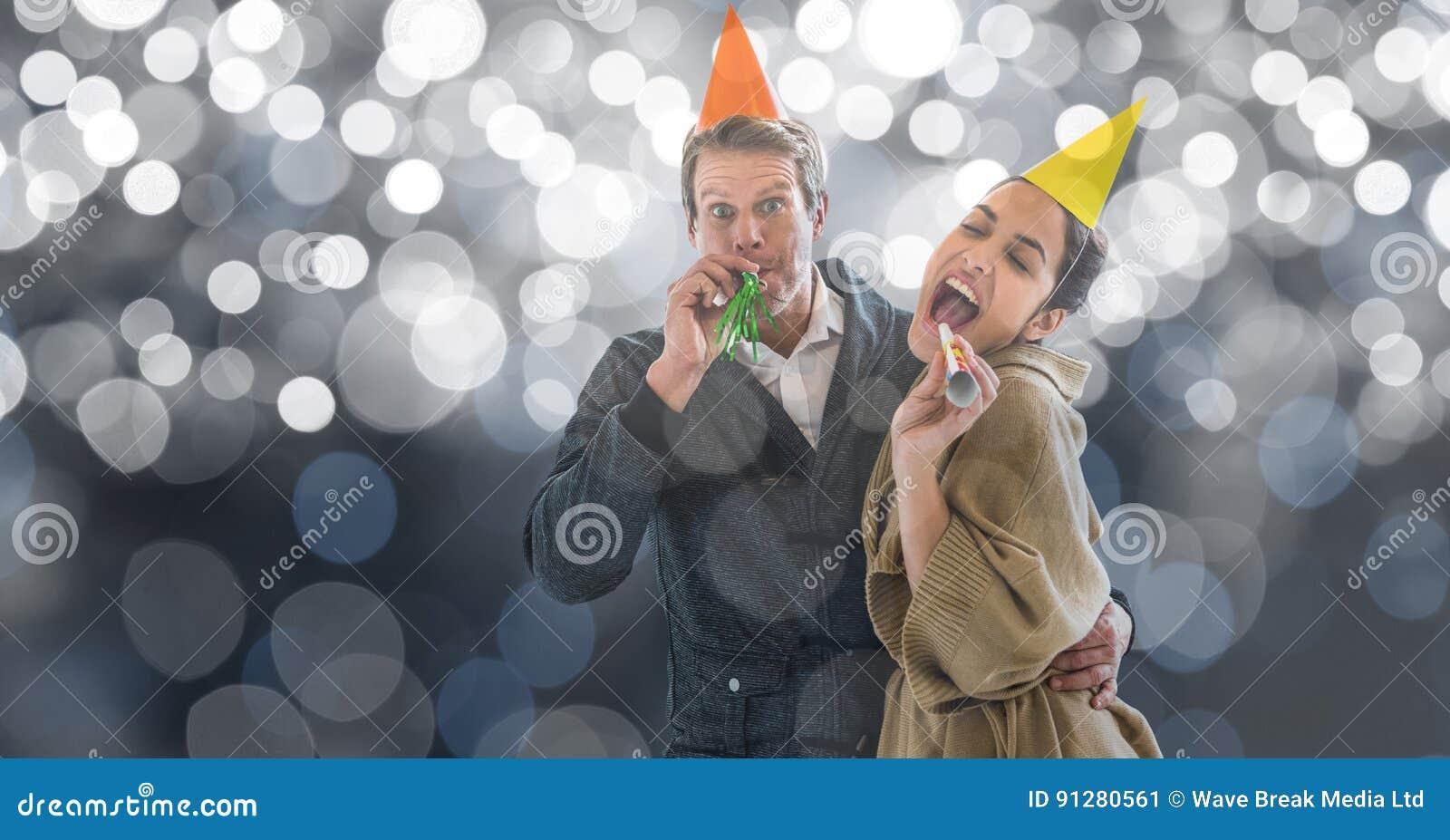 Lyckliga par som blåser partihorn mot suddighetsbakgrund