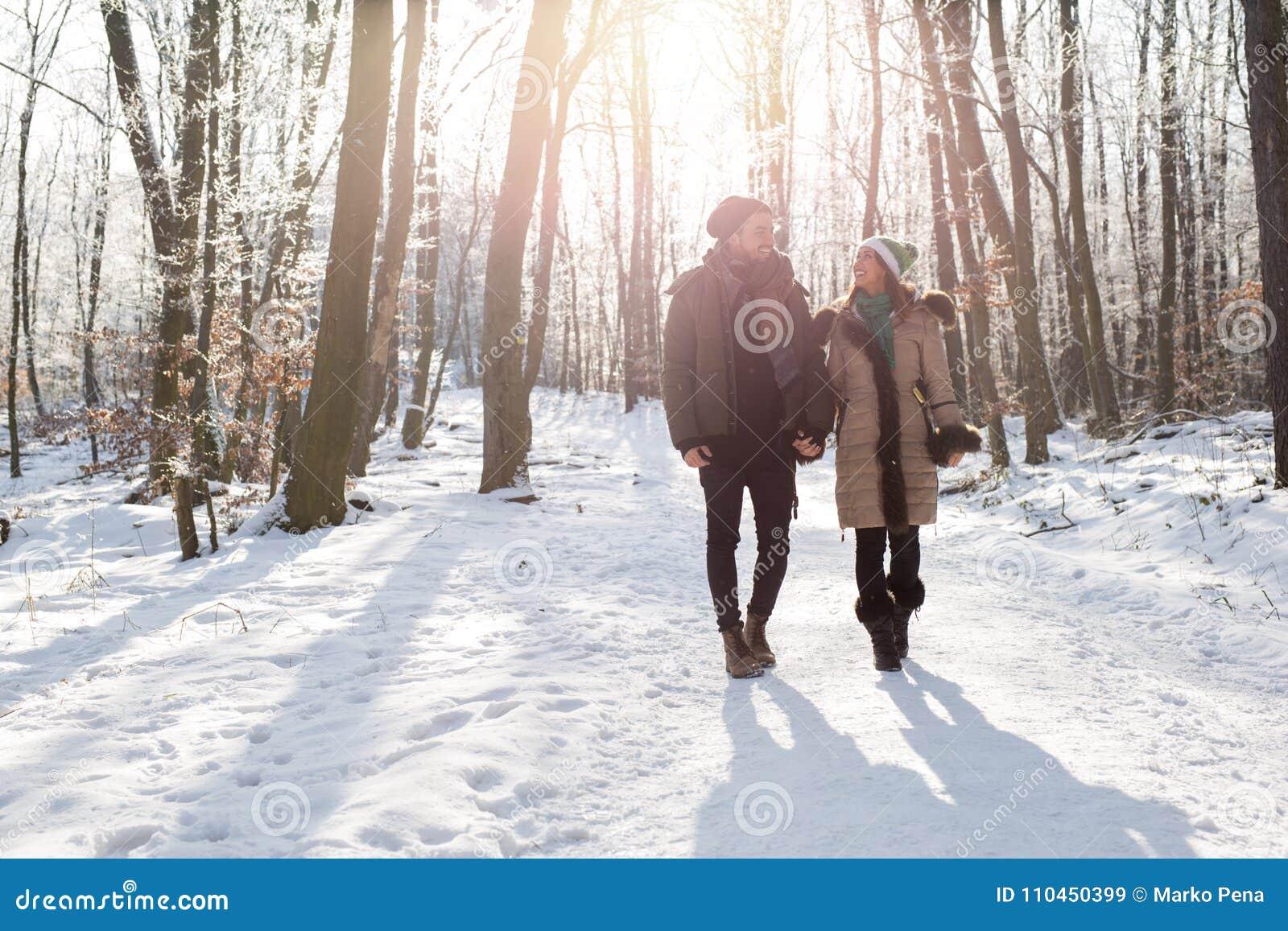 Lyckliga par som går i skogen på snövintertid