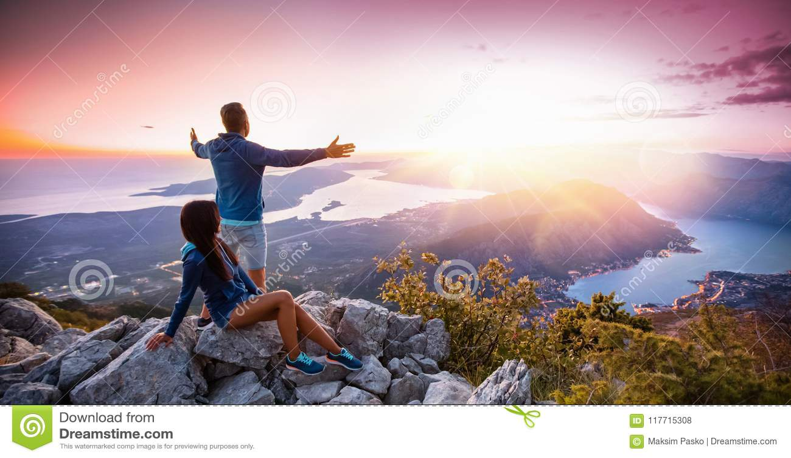 Lyckliga par som håller ögonen på solnedgången i bergen