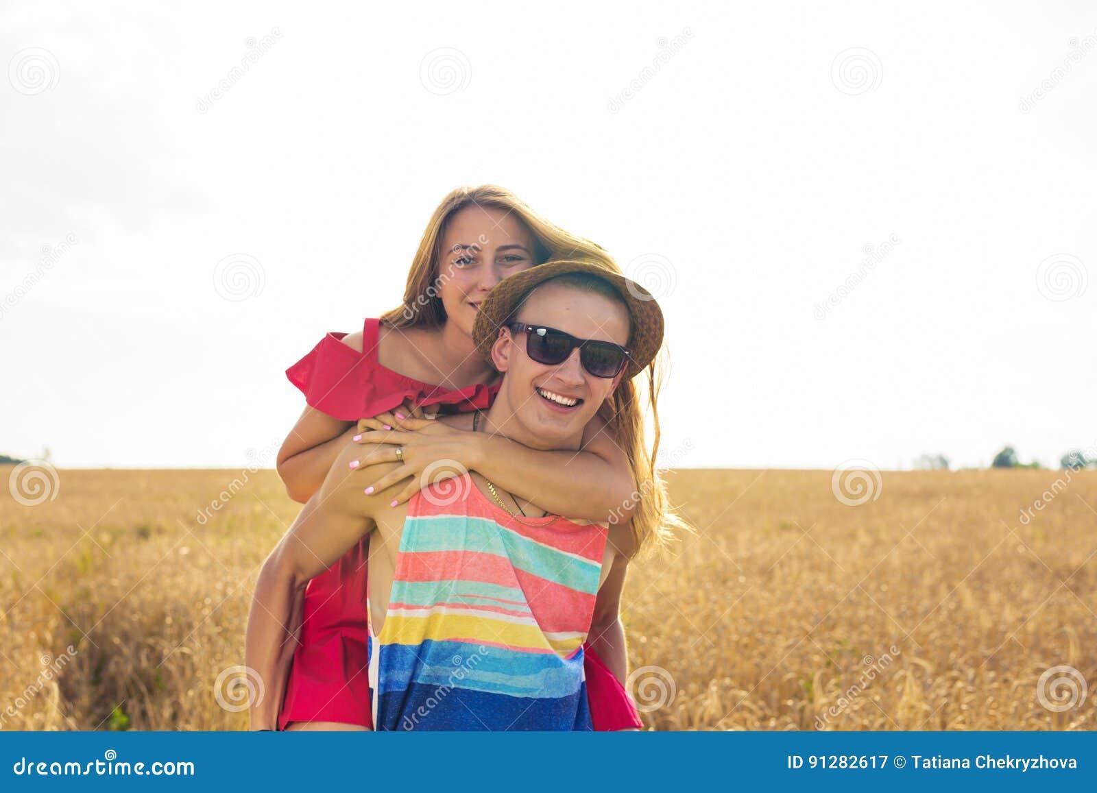 Lyckliga par som har rolig det fria på fält svart isolerad begreppsfrihet piggyback