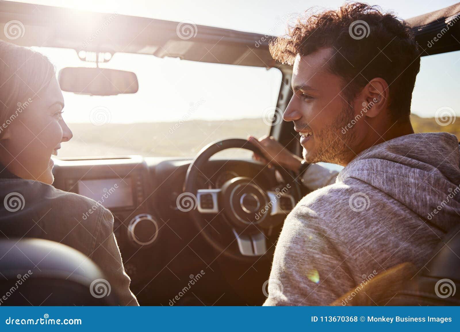Lyckliga par som kör i bil med den öppna soltaket, passagerare POV
