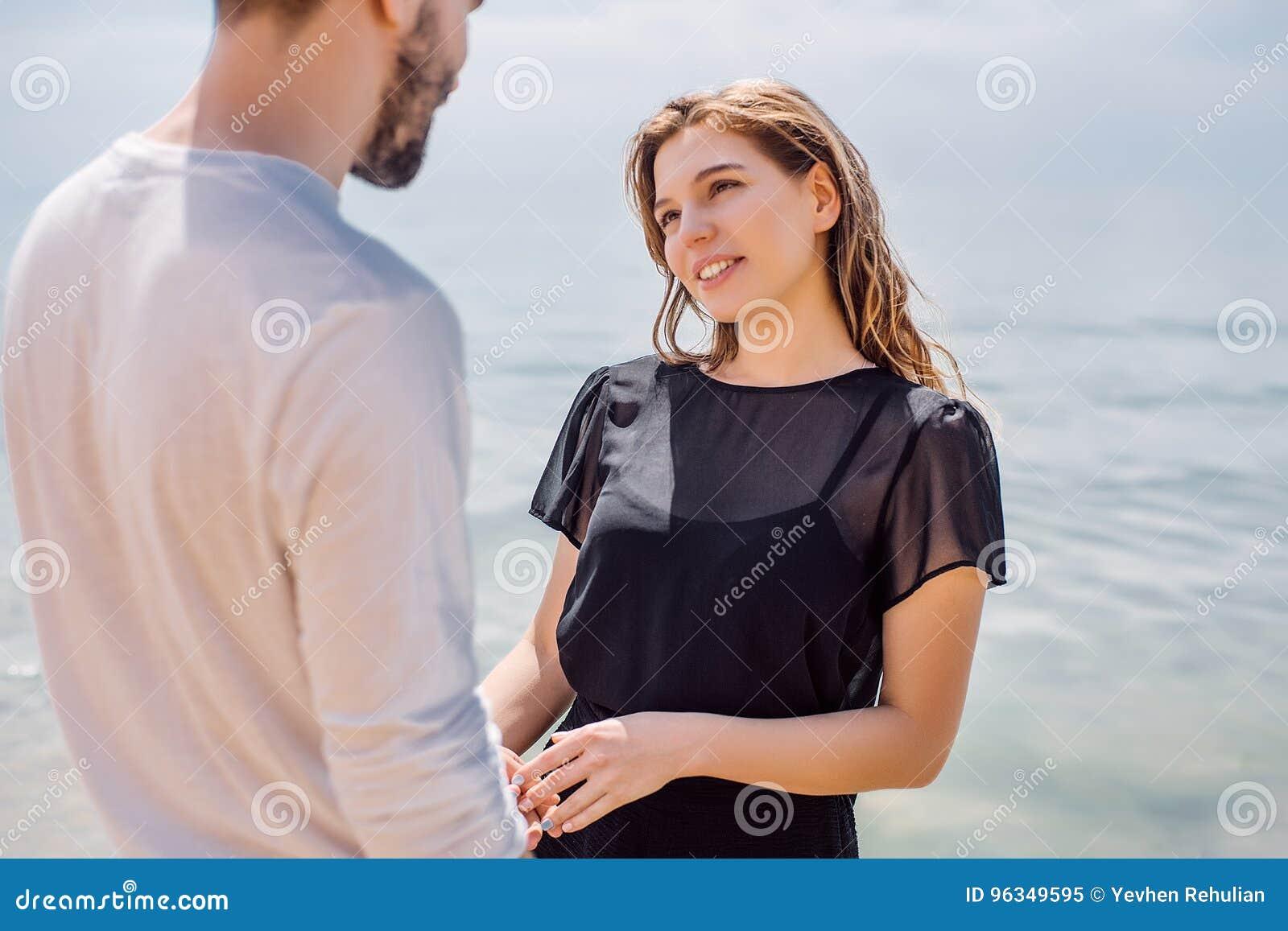 Lyckliga par som kramar på havet, sätter på land, vuxna människan, sommarferier