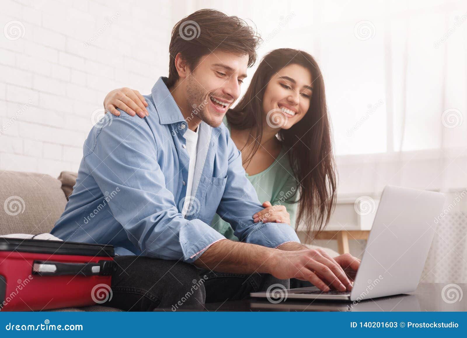 Lyckliga par som planerar loppet som direktanslutet bokar biljetter på bärbara datorn