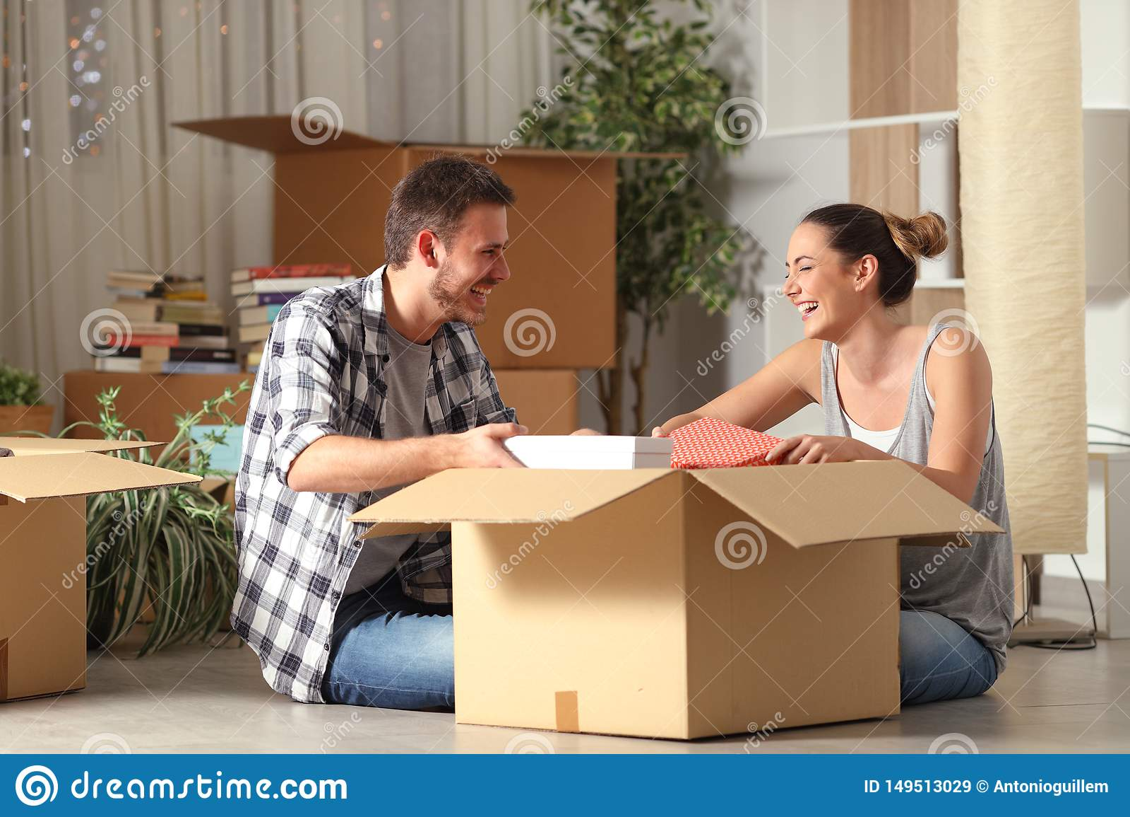 Lyckliga par som skrattar det unboxing r?rande huset f?r tillh?righeter
