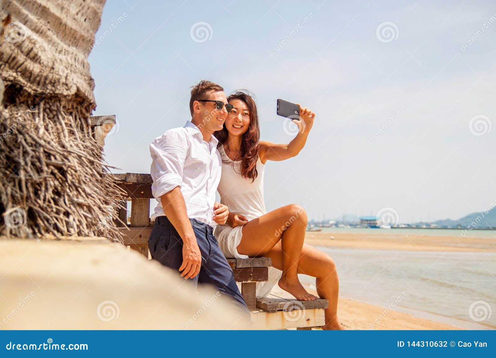Lyckliga par som tar ett foto på den vita stranden på bröllopsresaferie