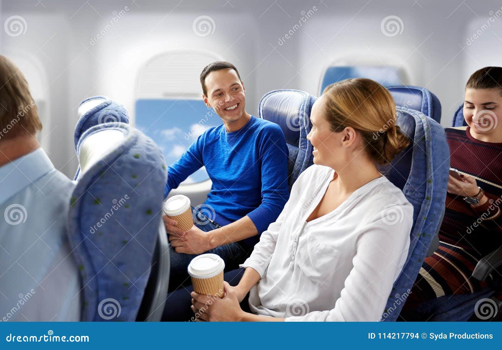 Lyckliga passagerare med kaffe som talar i nivå