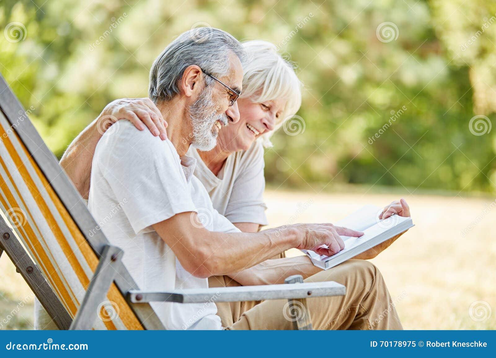 Lyckliga pensionärer som läser en bok