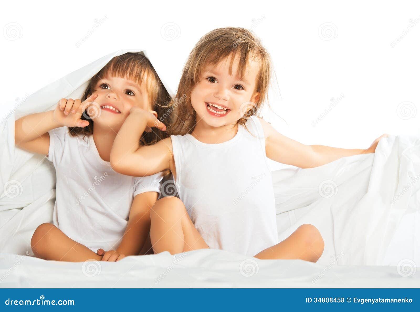 Lyckliga små flickor kopplar samman systern i säng under filten som den har