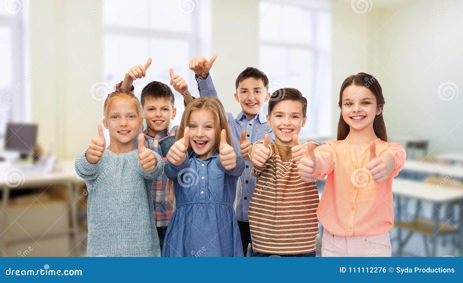 Lyckliga studenter som visar upp tummar på skolan