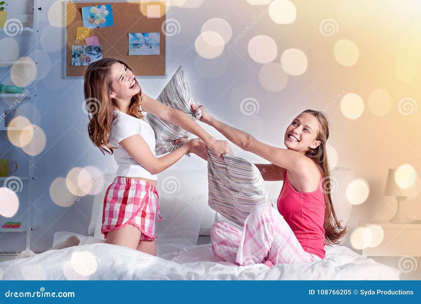 Lyckliga tonåriga flickavänner som hemma slåss kuddar