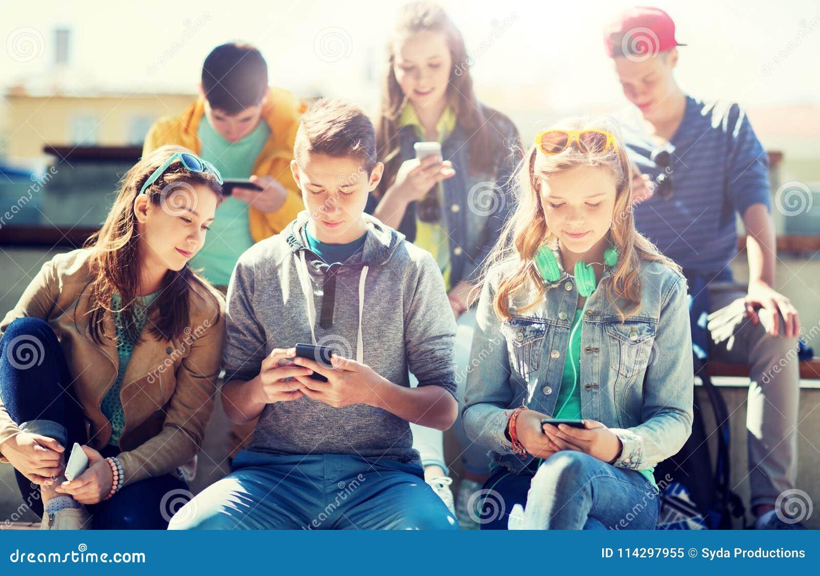 Lyckliga tonårs- vänner med smartphones utomhus