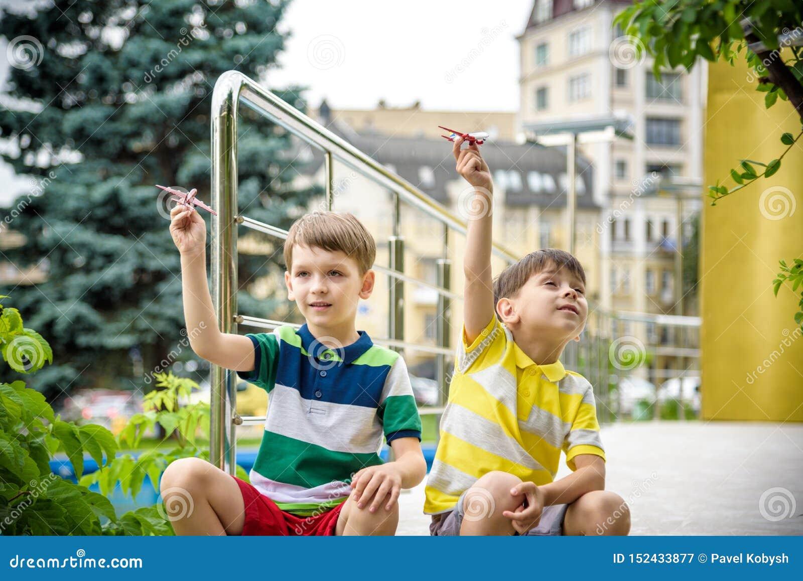 Lyckliga två broderungar som spelar med leksakflygplanet på varm sommardag Pojkar ser skalakopian av nivån Bästa barndom och lopp