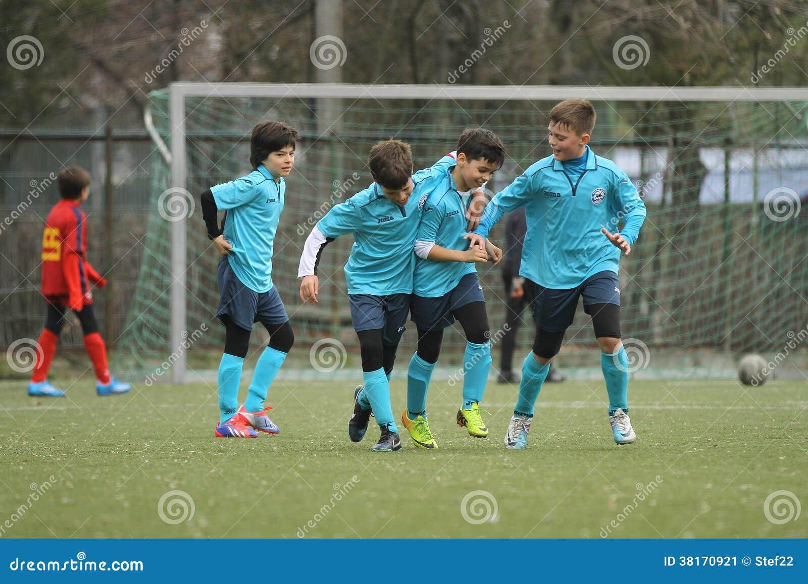 Lyckliga unga fotbollsspelare efter ett mål