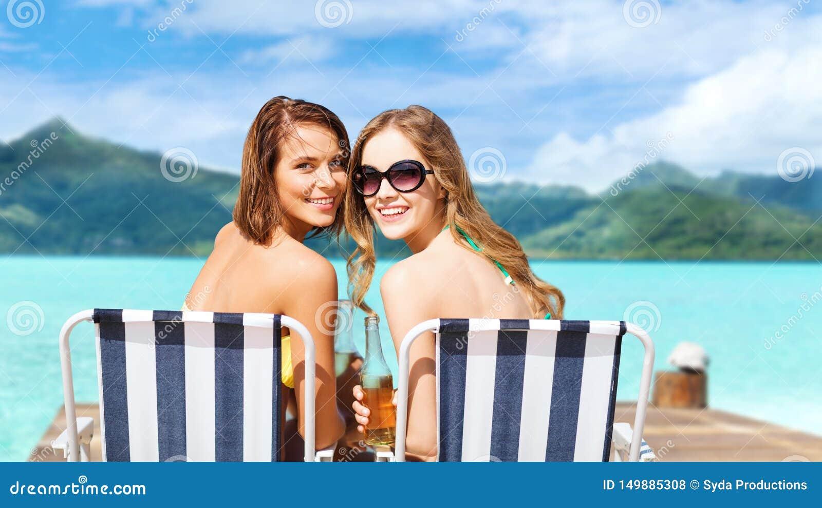 Lyckliga unga kvinnor i bikini med drinkar på stranden