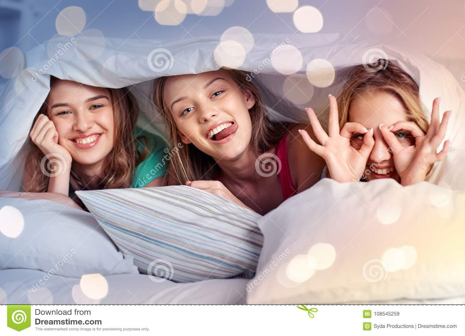 Lyckliga unga kvinnor i hemmastatt pajamaparti för säng