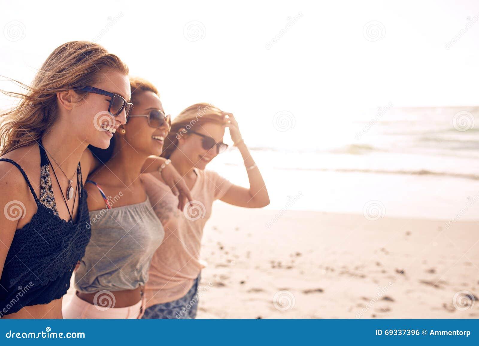 Lyckliga unga kvinnor som går på en strand