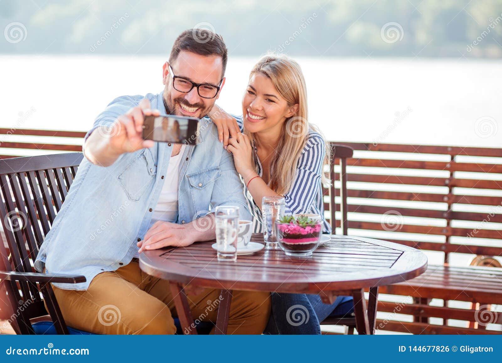 Lyckliga unga par som dricker kaffe i ett kafé som tar en selfie