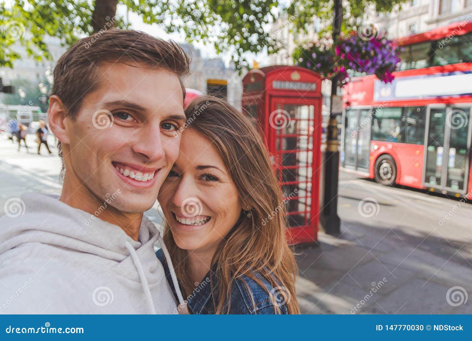 Lyckliga unga par som framme tar en selfie av en telefonask och en röd buss i London
