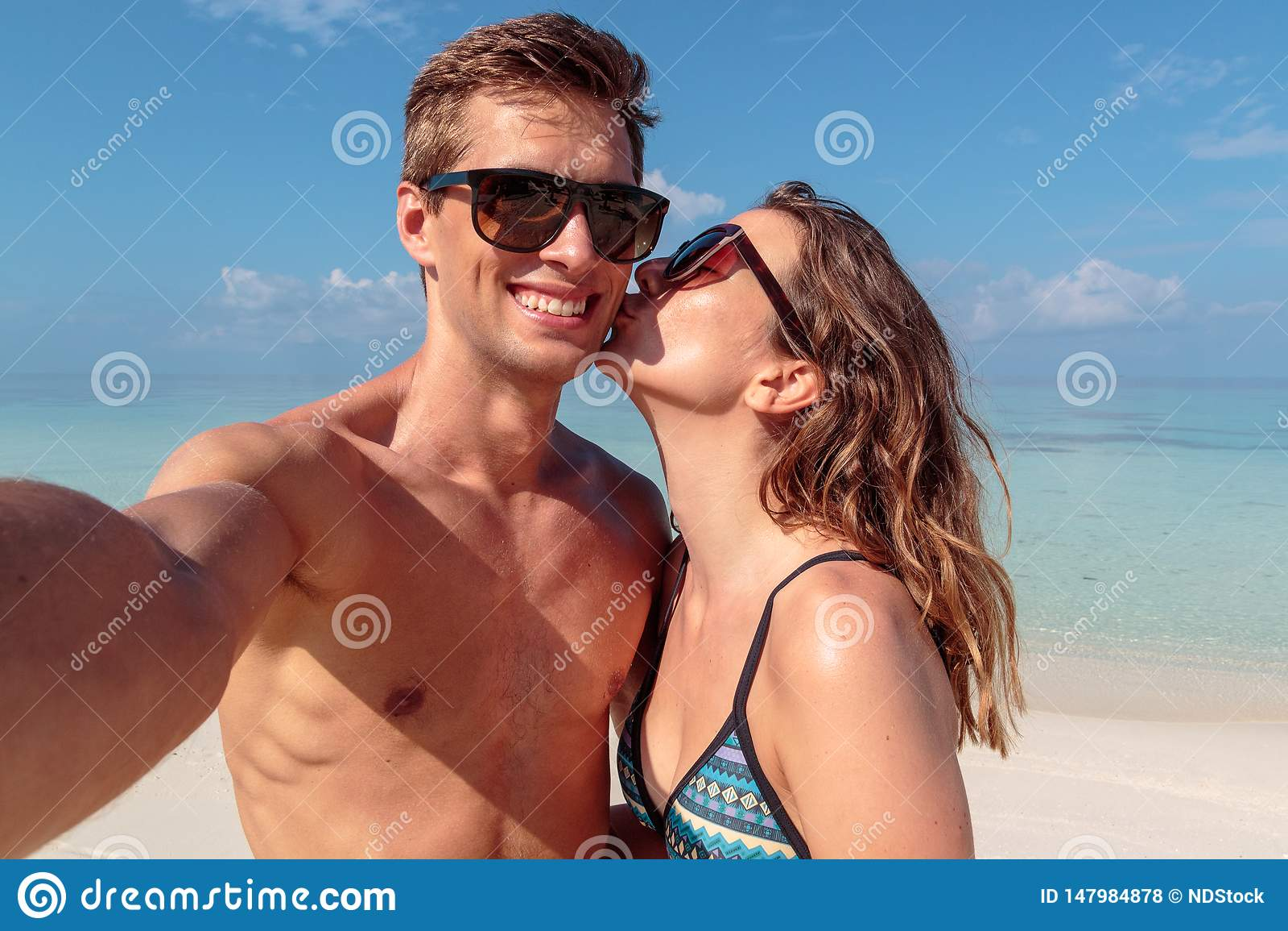 Lyckliga unga par som tar en selfie, klart bl?tt vatten som bakgrund Flicka som kysser hans pojkv?n