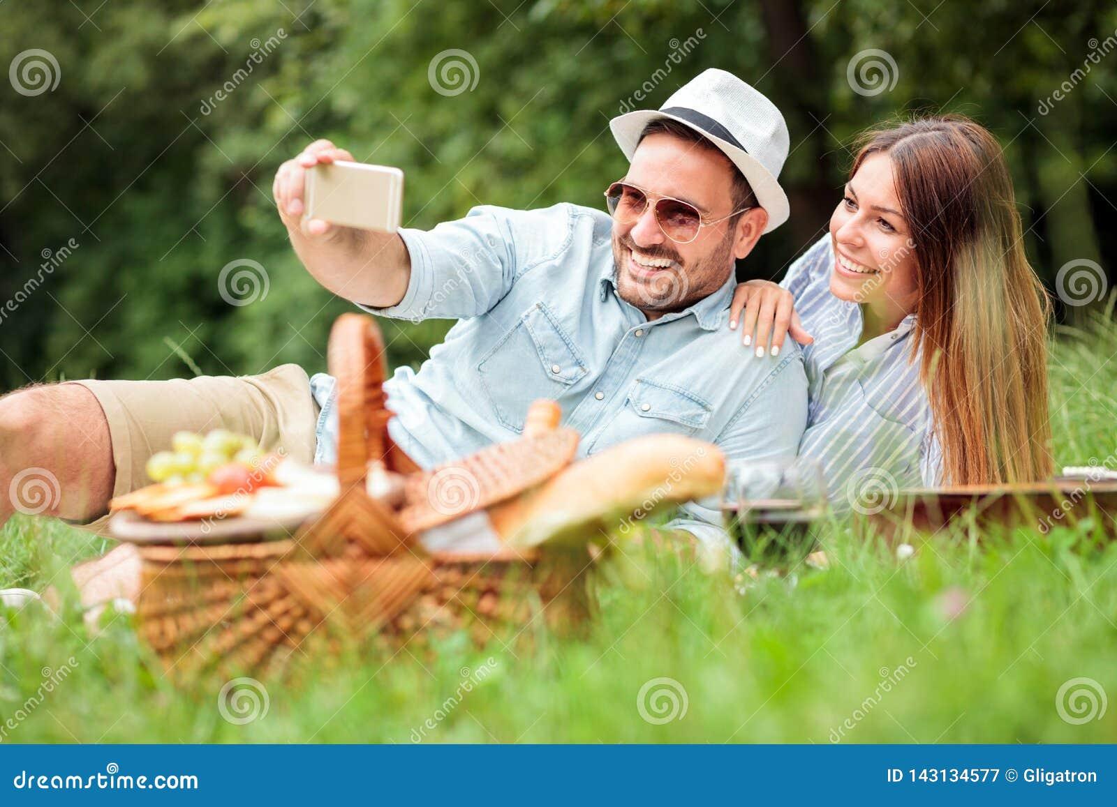 Lyckliga unga par som tar en selfie, medan tycka om picknicktid, parkerar in