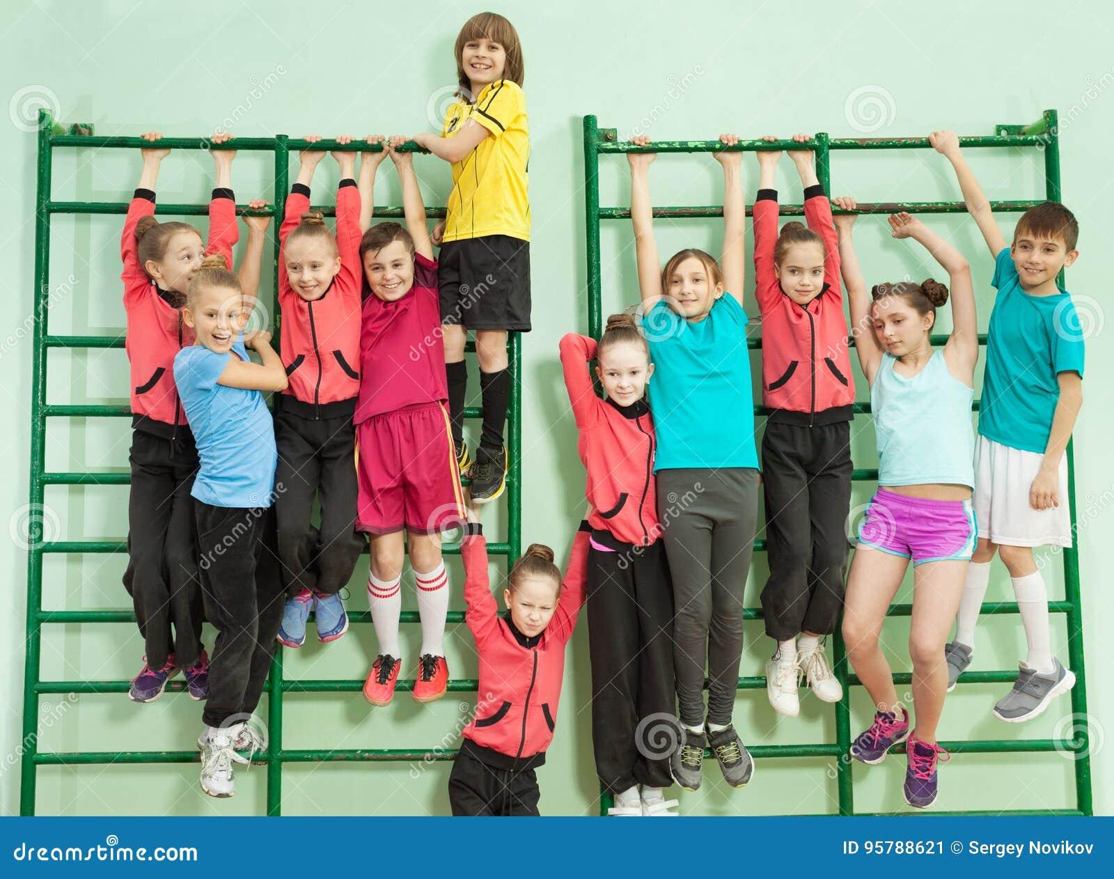 Lyckliga ungar som hänger på ribbstolen i skolaidrottshall