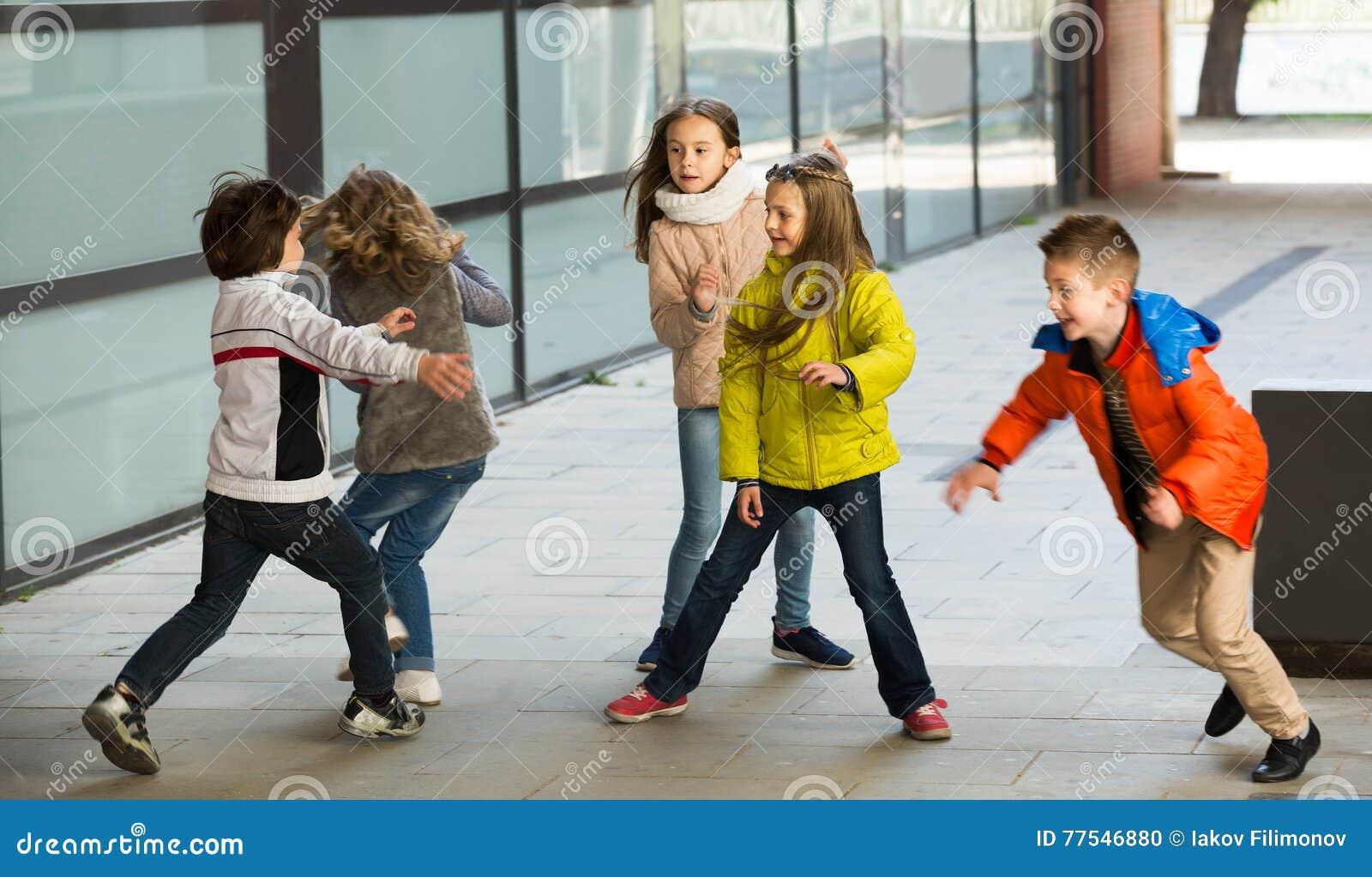 Lyckliga ungar som omkring kör, medan spela på etiketten