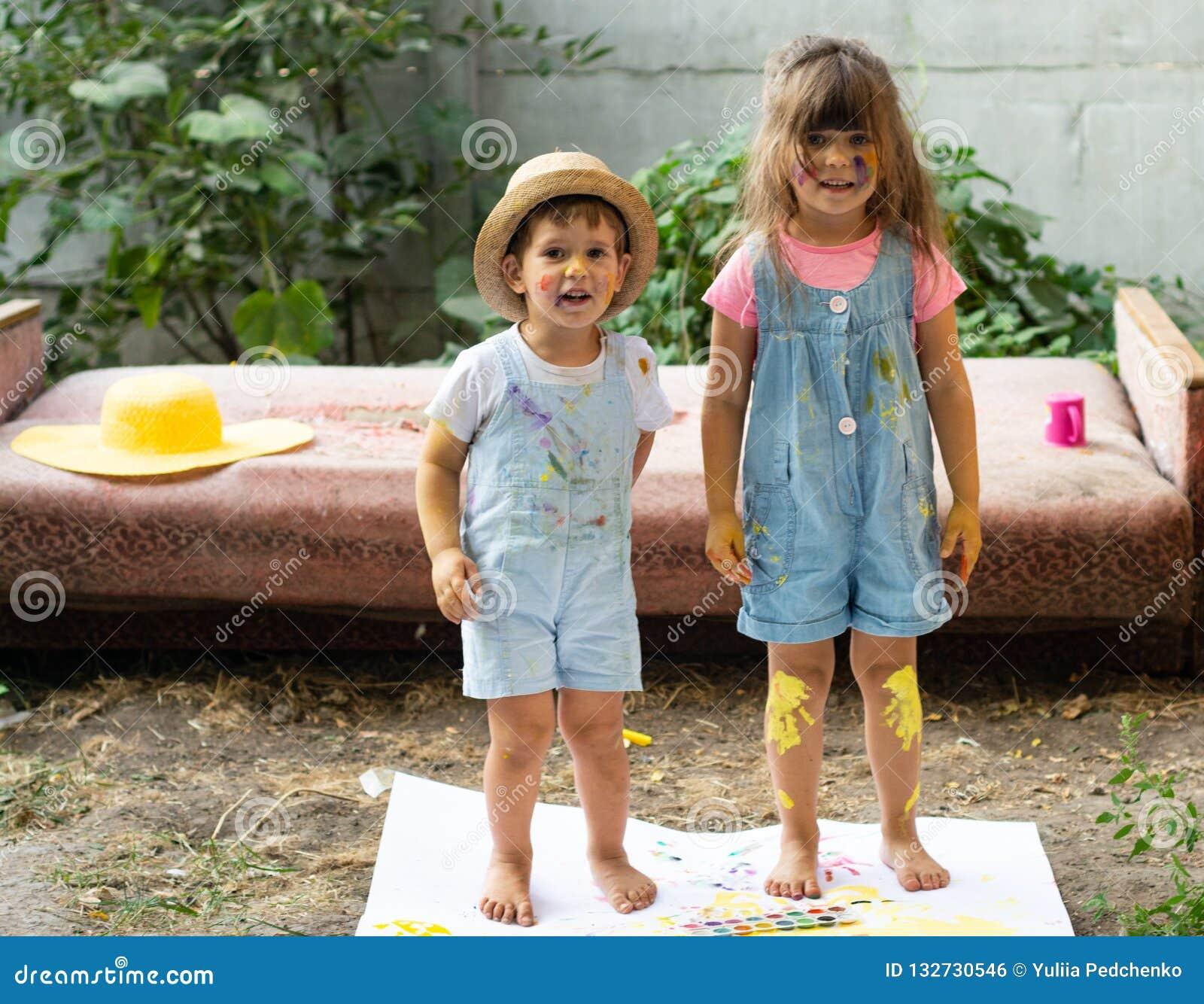 Lyckliga ungar som tillsammans gör konsthantverk Stående av den förtjusande lilla flickan och pojken som lyckligt ler, medan tyck