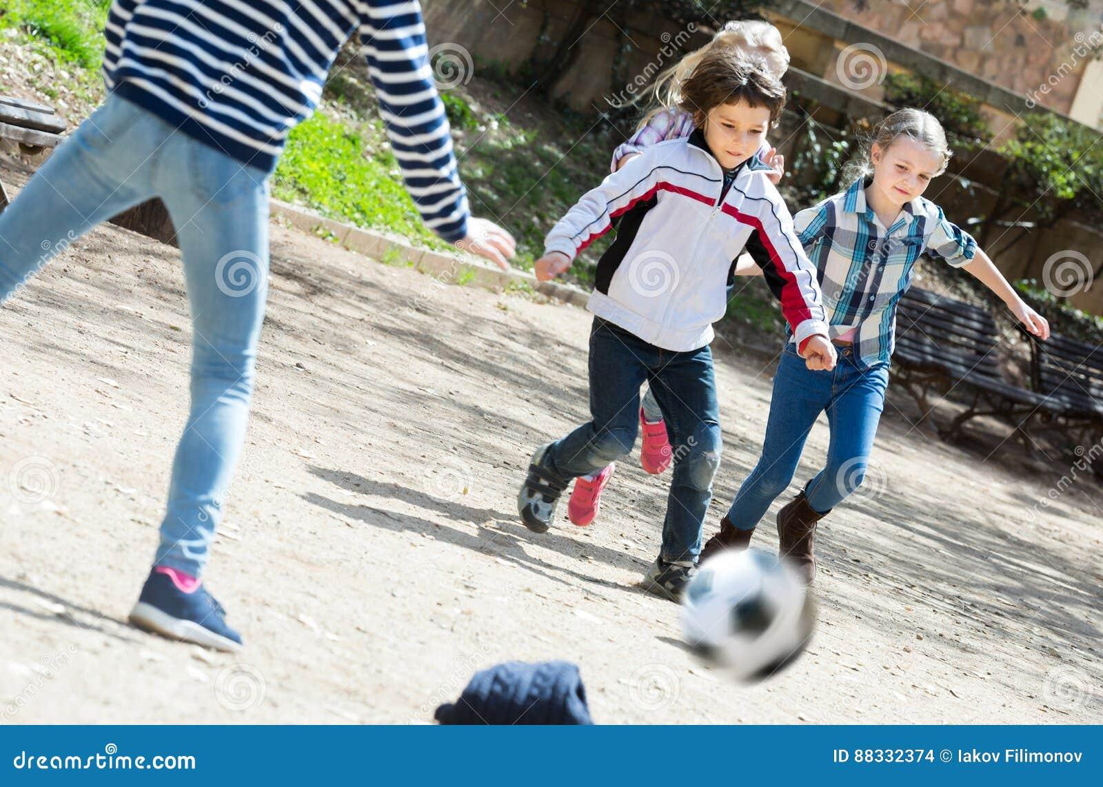Lyckliga ungar som utomhus spelar gatafotboll