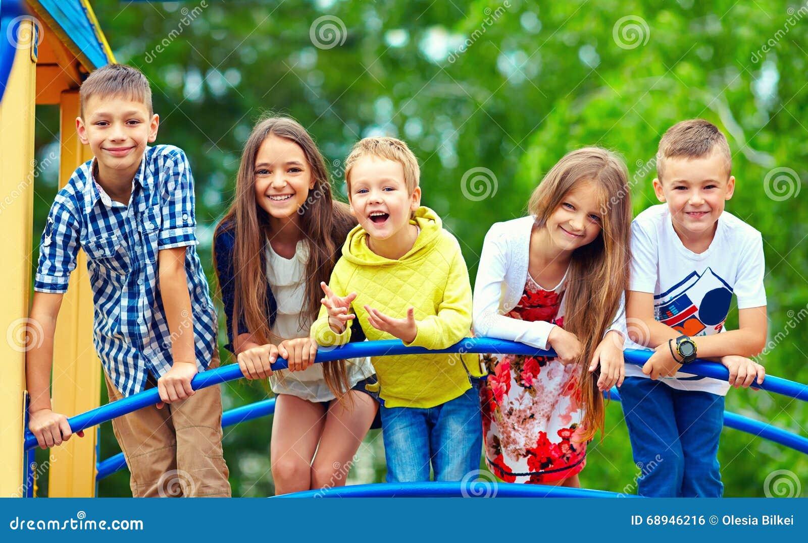 Lyckliga upphetsade ungar som har gyckel tillsammans på lekplats