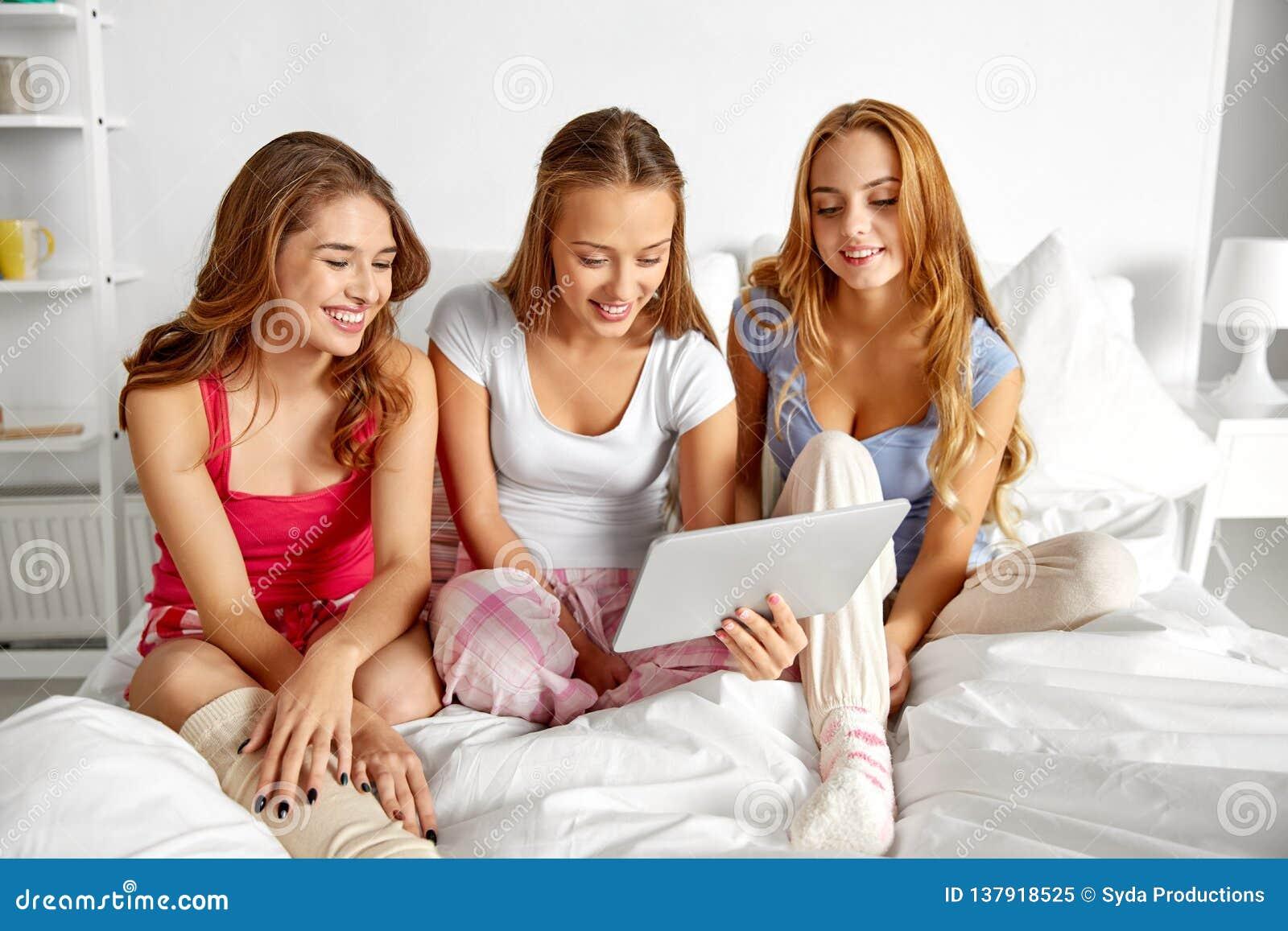 Lyckliga vänner eller tonåriga flickor med minnestavlaPC hemma