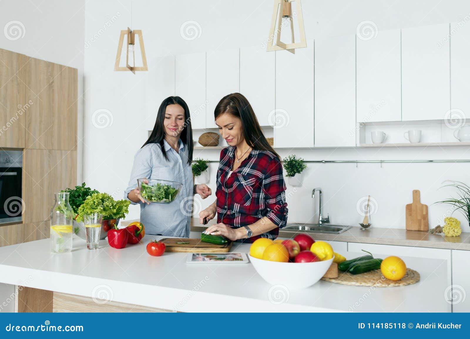 Lyckliga vänner för sund livsstil som talar laga mat grönsakhem K