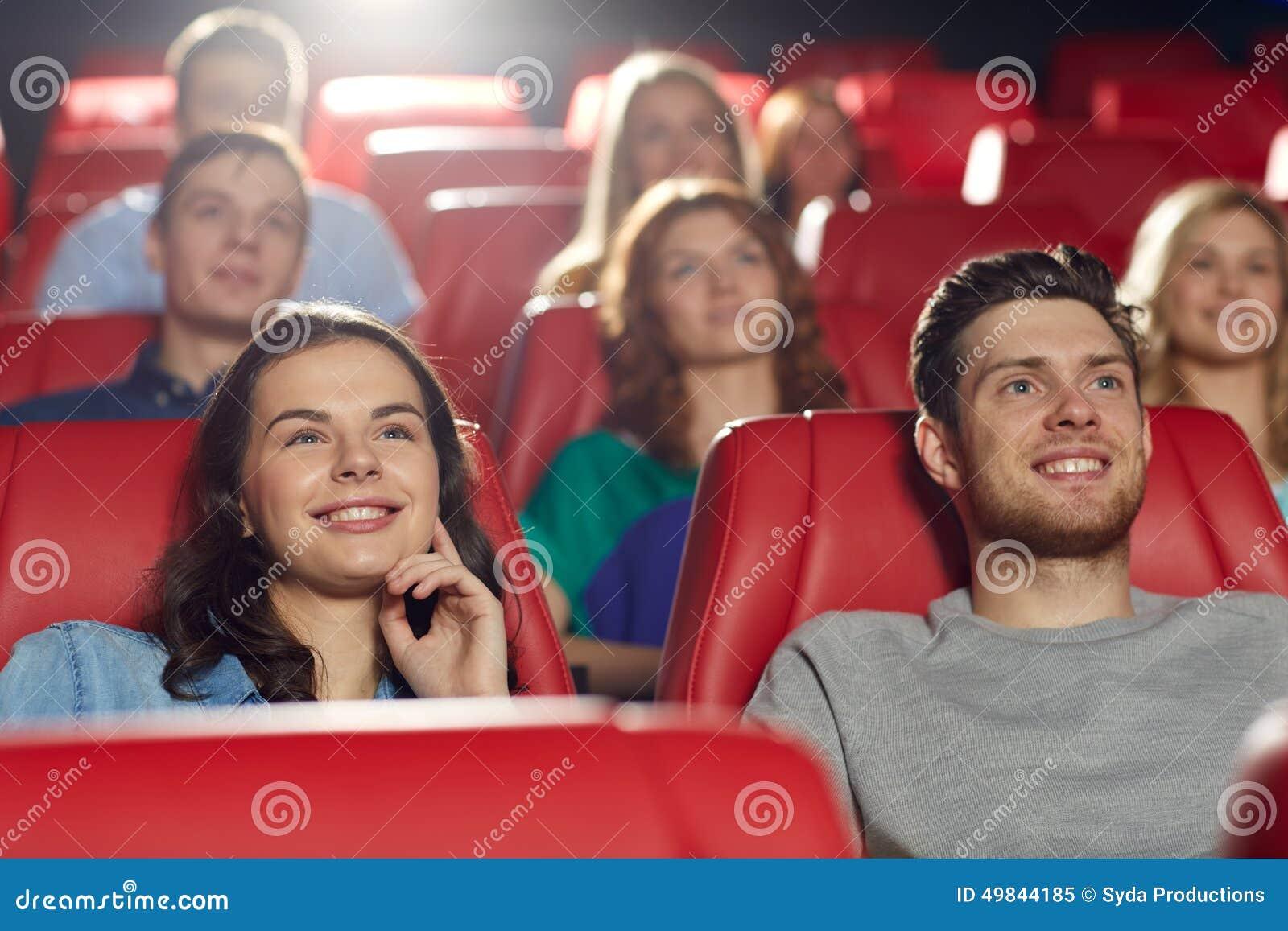Lyckliga vänner som håller ögonen på film i teater