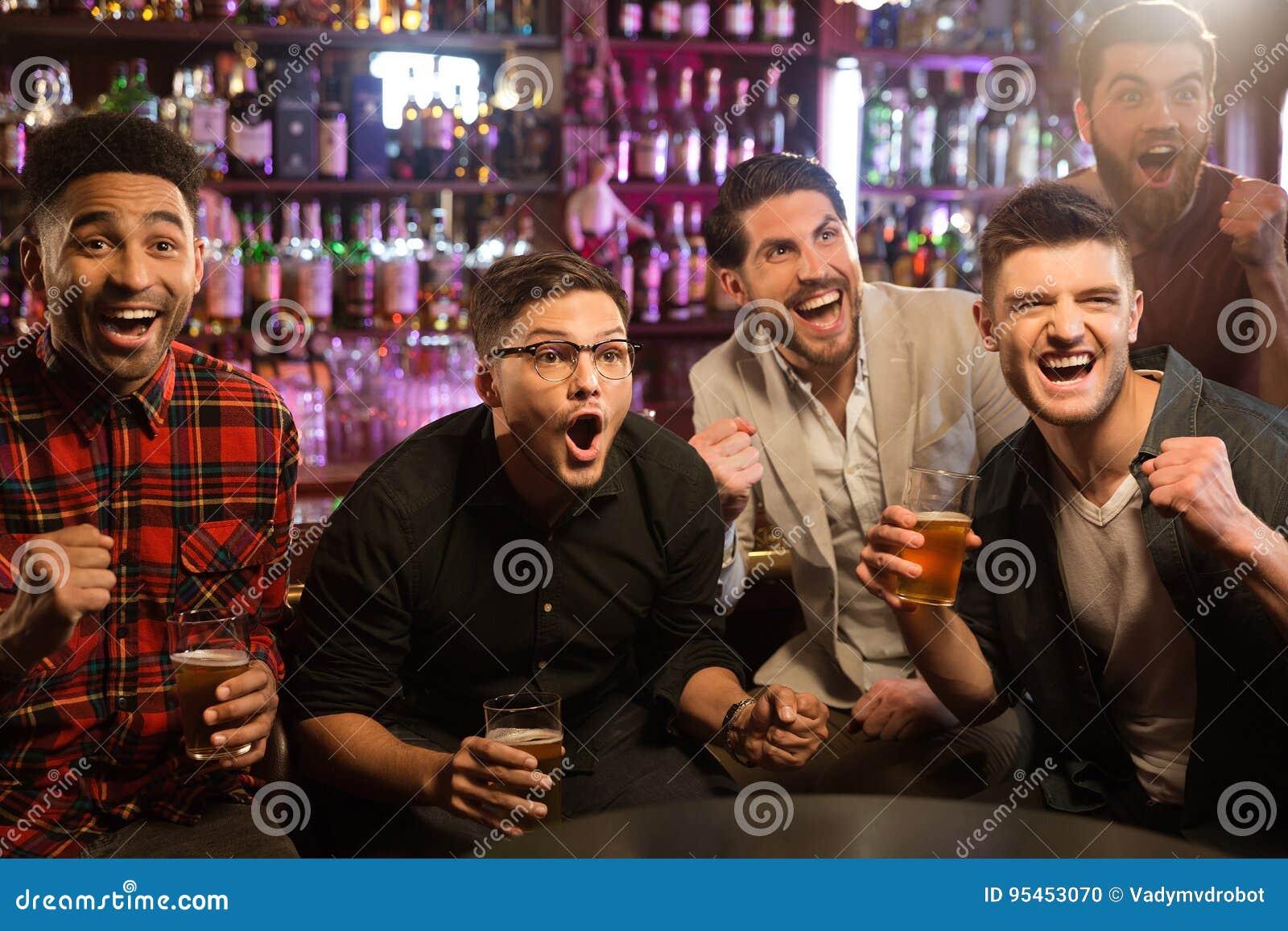 Lyckliga vänner som har gyckel i bar