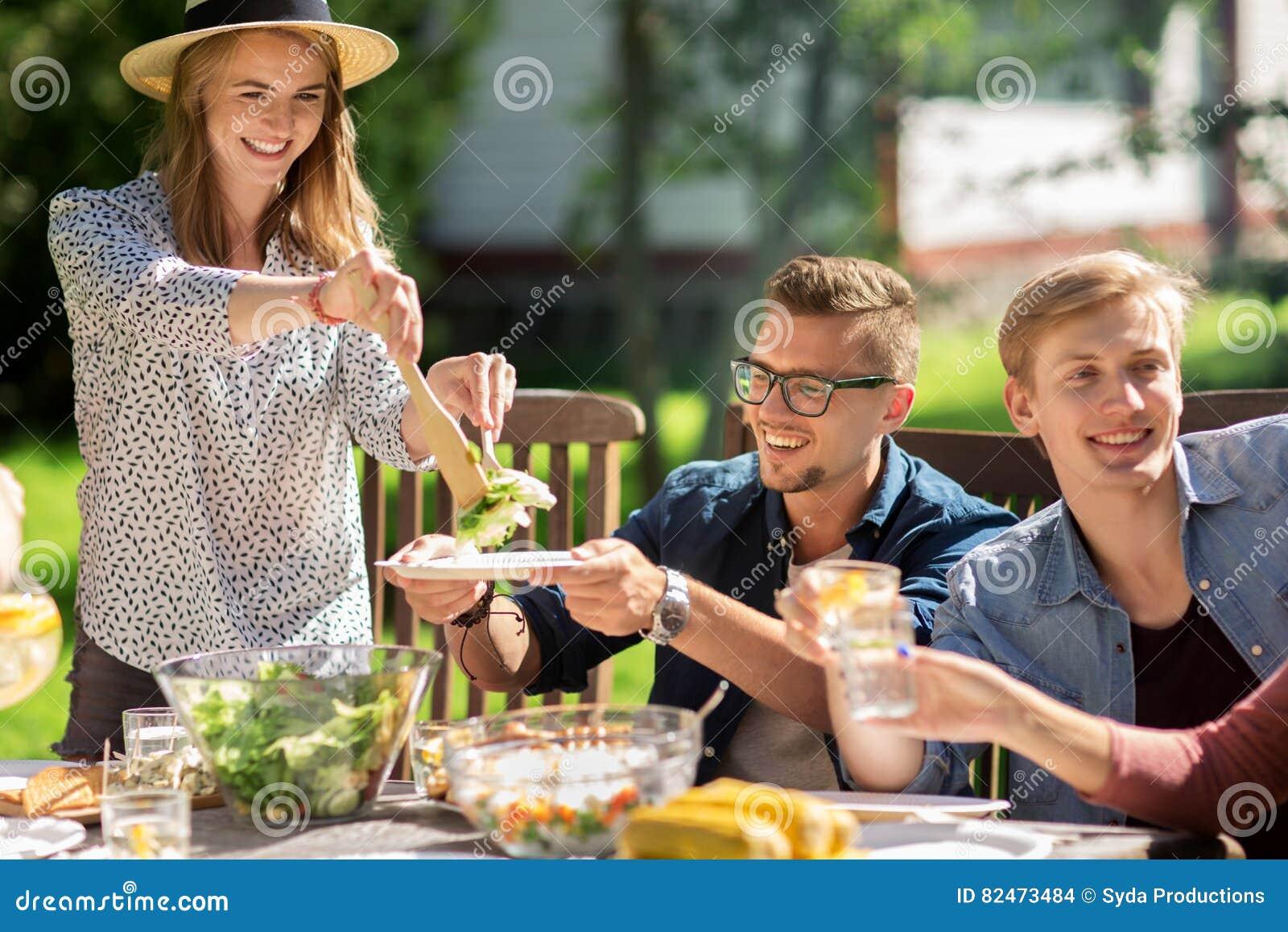 Lyckliga vänner som har matställen på det trädgårds- partiet för sommar