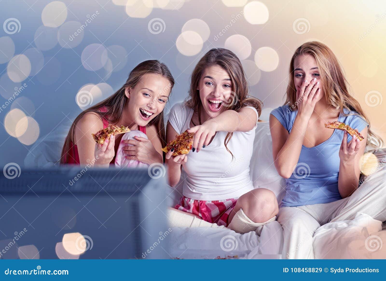 Lyckliga vänner som hemma äter pizza och håller ögonen på tv