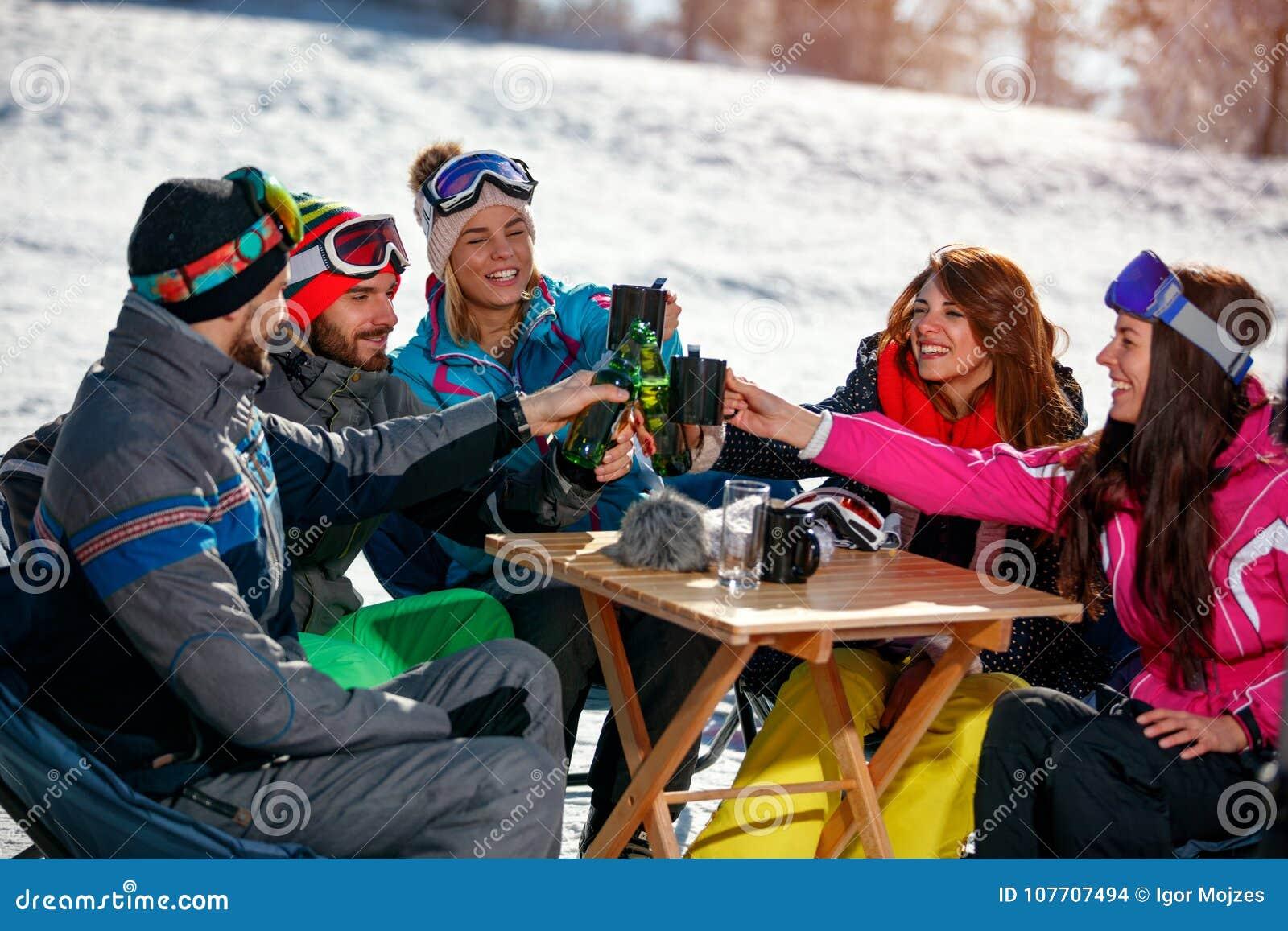 Lyckliga vänner som hurrar med drinken efter skida dag i kafé på sk