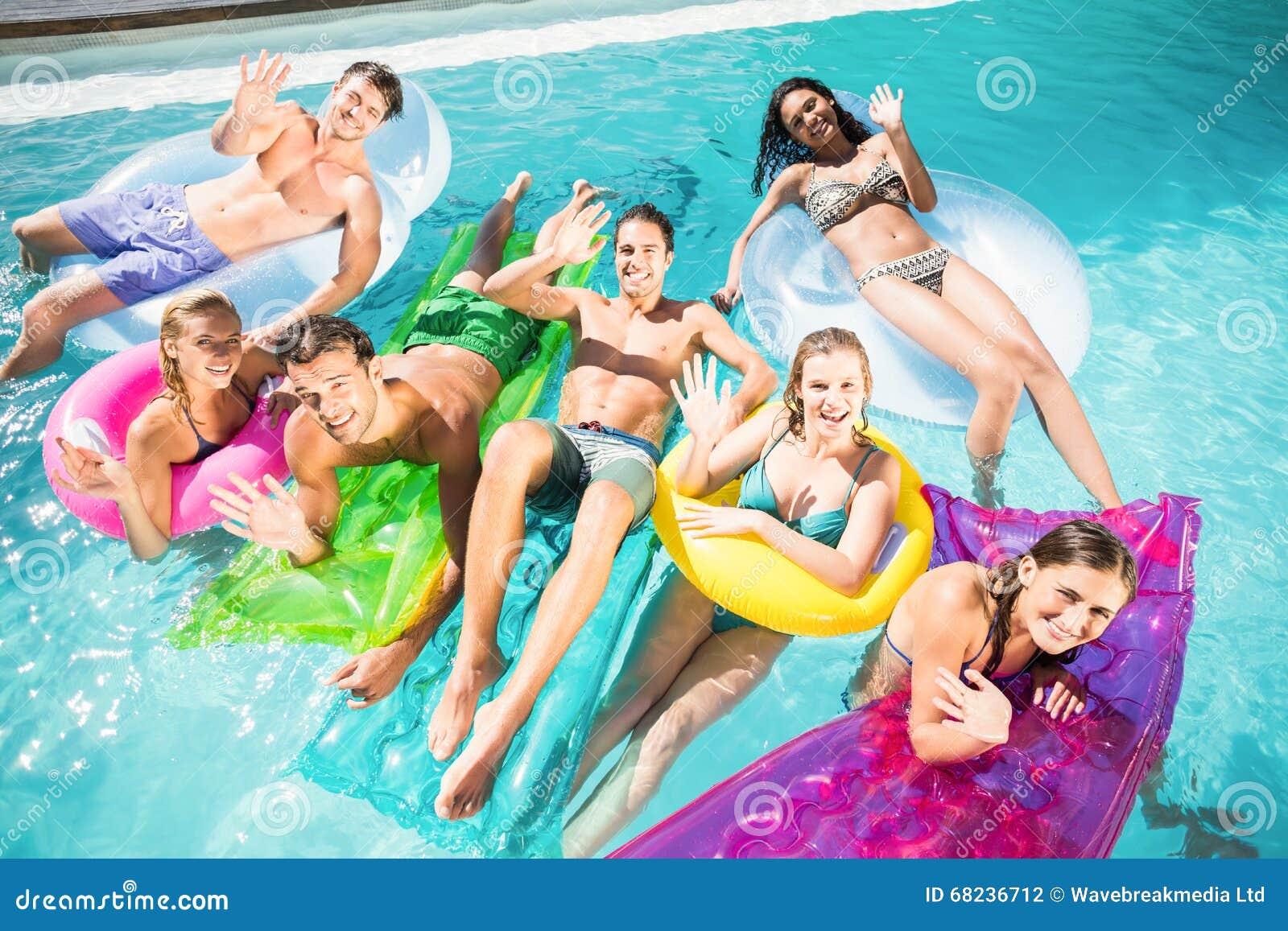 Lyckliga vänner som tycker om i simbassängen