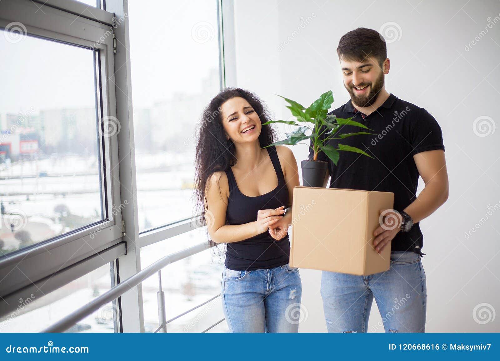 Lyckliga vuxna par som är rörande ut eller in till det nya hemmet