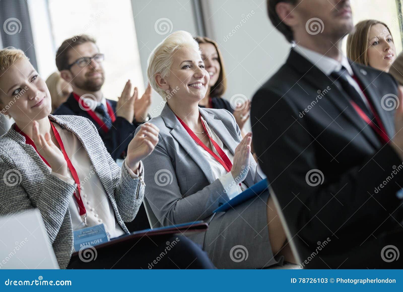 Lyckligt affärsfolk som applåderar under seminarium