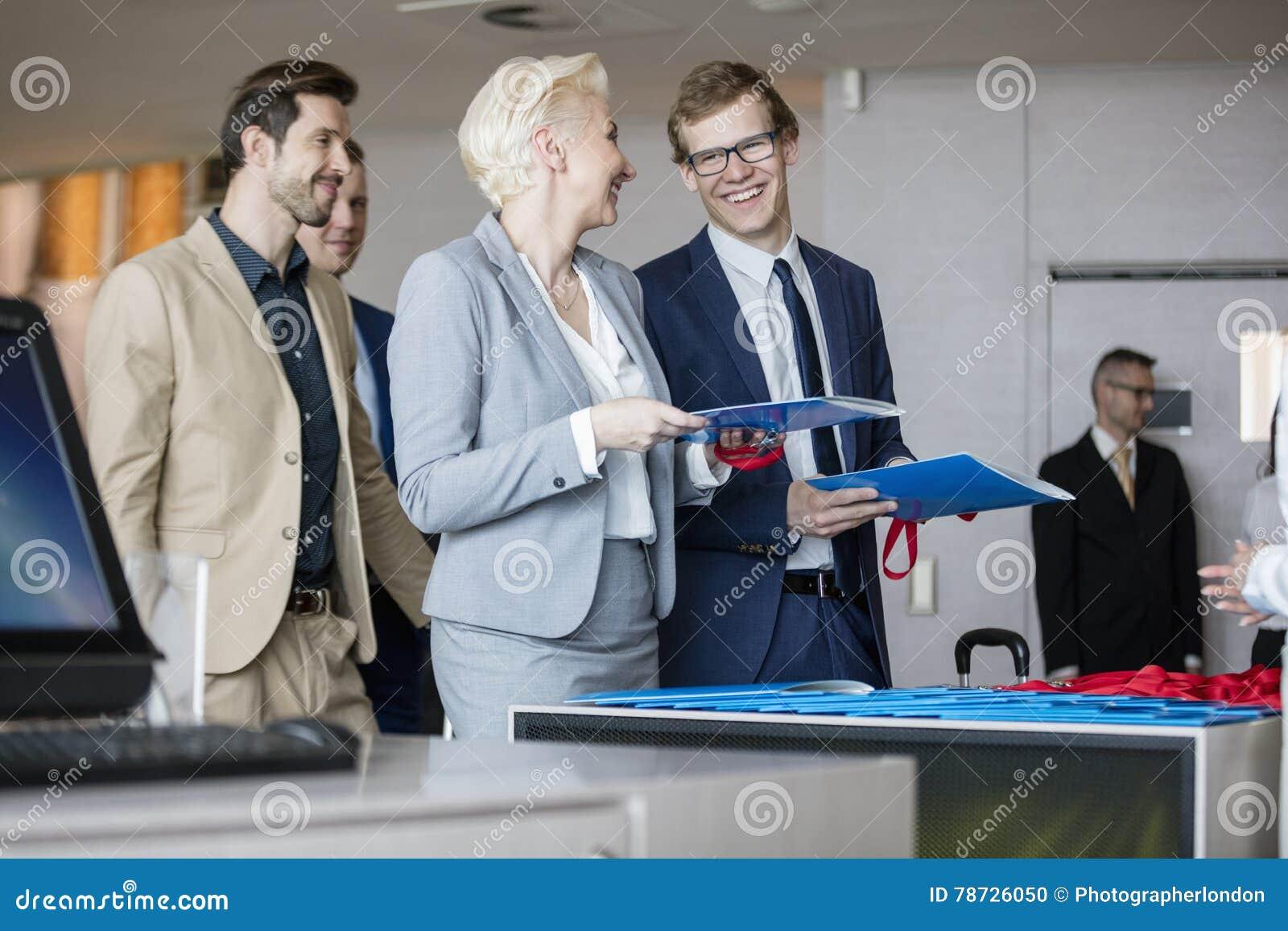 Lyckligt affärsfolk som talar, medan hållande mappar på mottagandet kontrar i konventcentrum