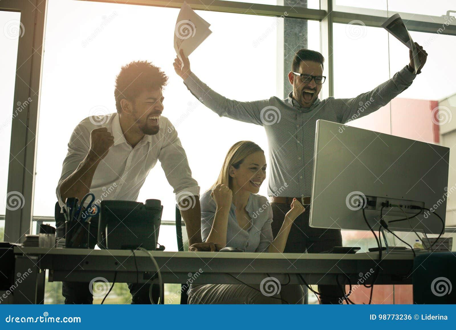 Lyckligt affärsfolk som tycker om i lyckat jobb