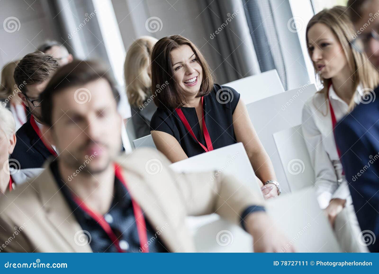 Lyckligt affärskvinnasammanträde med kollegor i seminariumkorridor