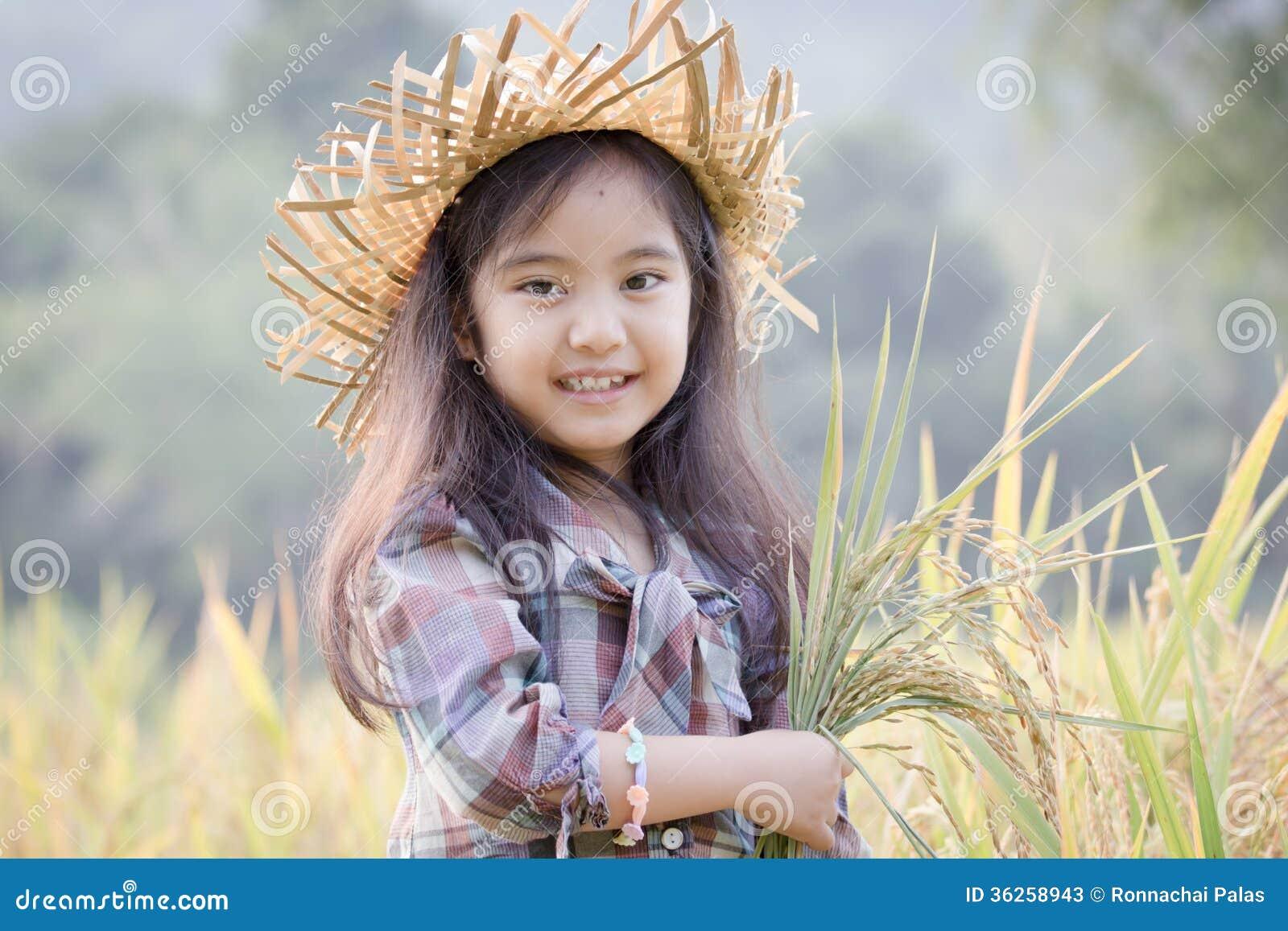 Lyckligt asiatiskt barn i risfält