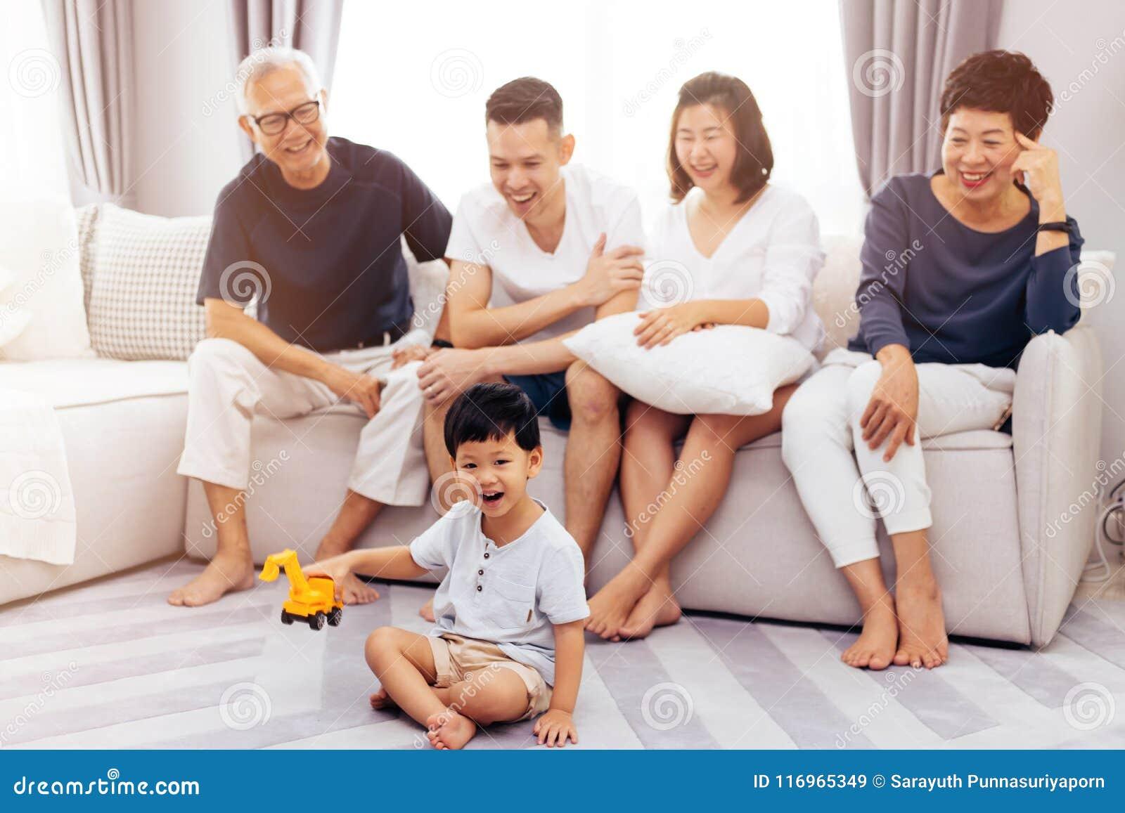 Lyckligt asiatiskt storfamiljsammanträde på soffan tillsammans och det hållande ögonen på lilla barnet som spelar leksaken på gol