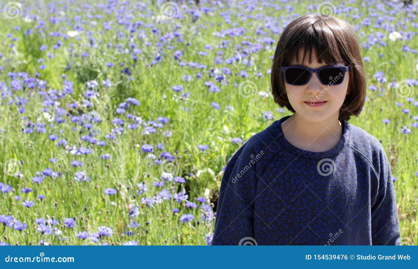 Lyckligt barn över en blom- fältbakgrund för solig lantlig blåklint
