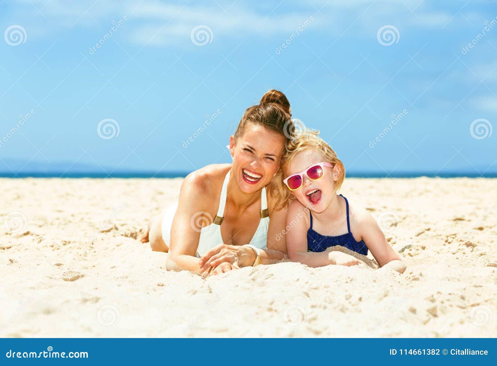 Lyckligt barn moder och barn i baddräkt som lägger på seacoasten