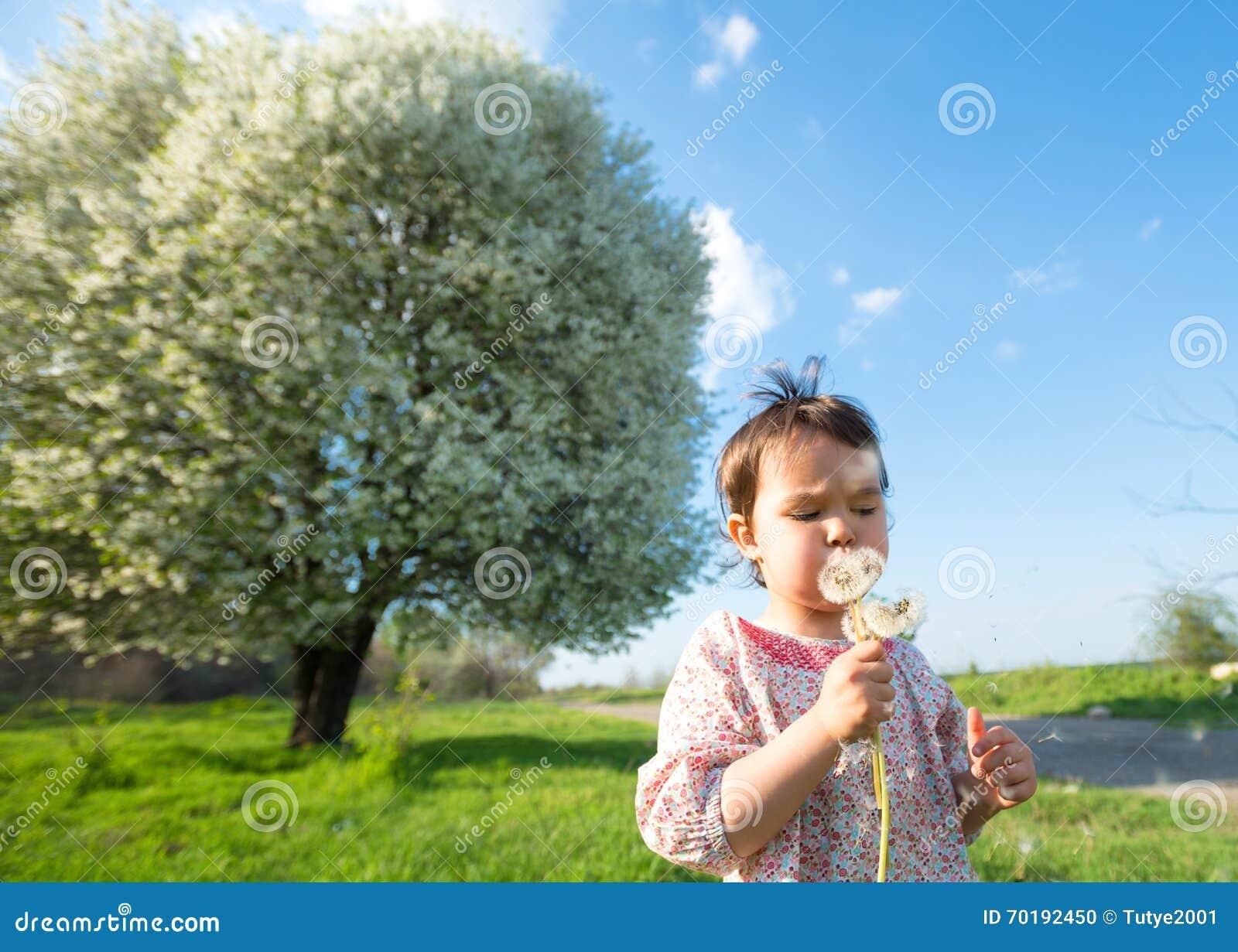 Lyckligt barn som utomhus blåser maskrosen i vår