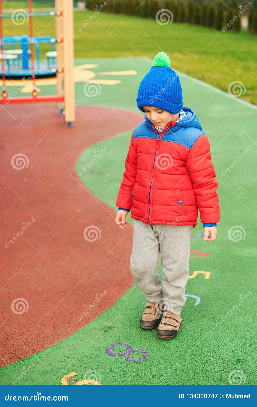 Lyckligt barn utomhus Gullig pys som spelar på färgrik modern lekplats Barnet har gyckel i kall tid lyckligt sunt