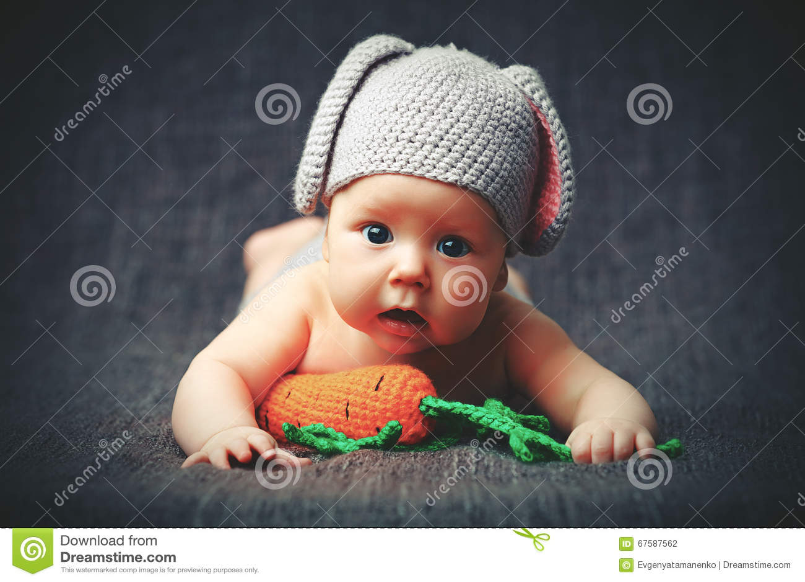 Lyckligt behandla som ett barn barnet kostymerar in en kaninkanin med moroten på en grå färg