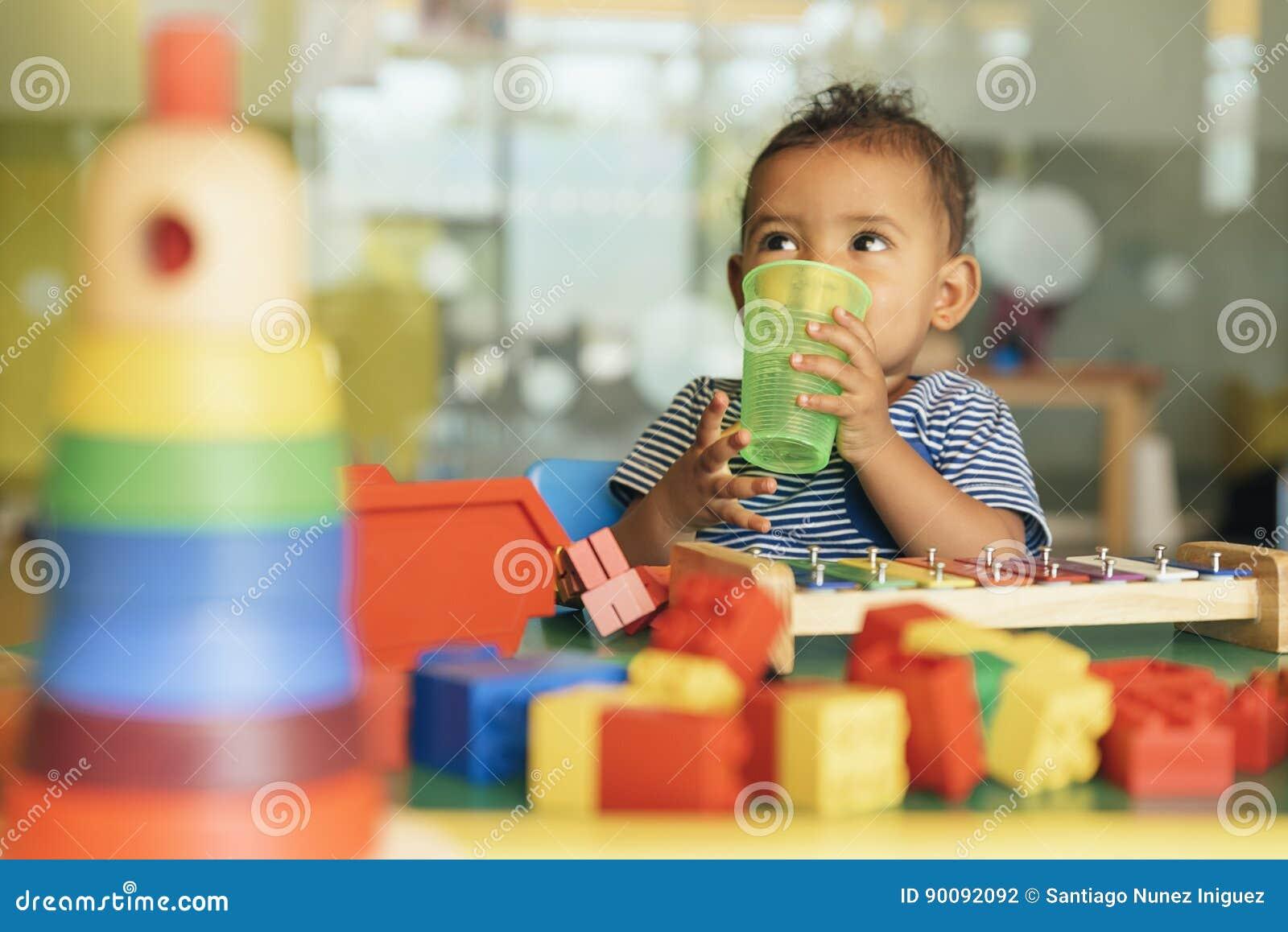Lyckligt behandla som ett barn dricksvatten och att spela